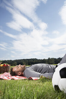 Germany, Cologne, Man relaxing on picnic blanket - PDF000393
