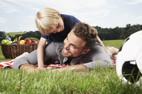 Germany, Cologne, Father and son playing around on picnic blanket - PDF000396