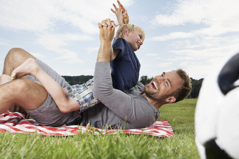 Germany, Cologne, Father and son playing around on picnic blanket - PDF000399