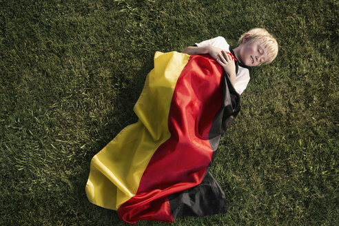 Germany, Cologne, Young football fan sleeping wrapped in German Flag - PDF000411