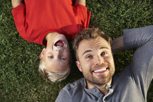 Germany, Cologne, Father and son lying in meadow - PDF000414