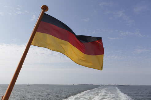 Germany, Lower Saxony, East Frisia, Langeoog, ferry boat with German flag - JATF000303