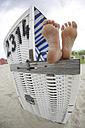 Germany, Lower Saxony, East Frisia, Langeoog, feet on an armrest of a roofed wicker beach chair - JATF000346