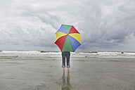 Germany, Lower Saxony, East Frisia, Langeoog, woman with open umbrella standing at the beach - JATF000314