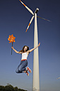 Germany, North Rhine Westphalia, Neuss, female teenager at wind farm jumping in the air with windmill in her hand - JATF000354
