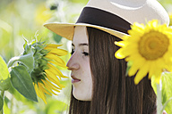 Germany, Cologne, young woman with hat and sunflower - JATF000331