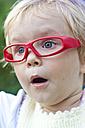 Germany, Schleswig-Holstein, Kiel, portrait of astonished little girl with red glasses - JFEF000224