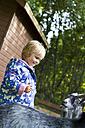 Denmark, Langeland, little girl watching at goat - JFE000227