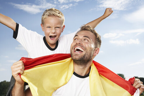 Germany, Cologne, Father and son cheering in football outfit - PDF000445