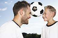 Germany, Cologne, Father and son playing soccer - PDF000448