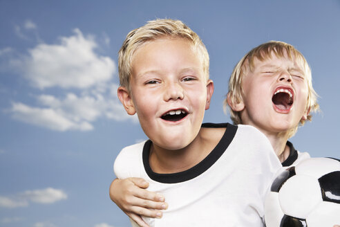 Germany, Cologne, Two boys playing football, wearing football shirts - PDF000454