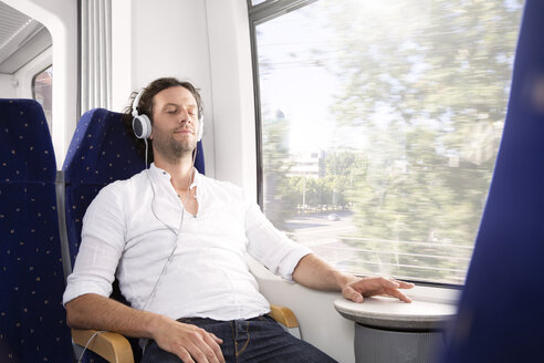 Man with headphones in a train - KFF000259