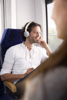 Man with headphones in a train smiling at woman - KFF000256
