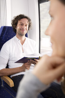 Man reading book in a train - KFF000280