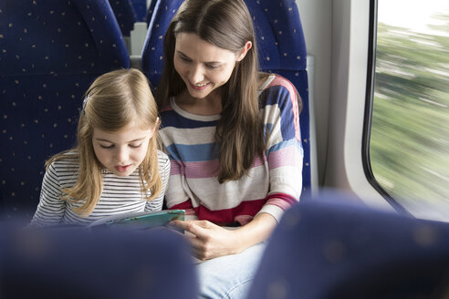 Mother and daughter reading book in a train - KFF000278