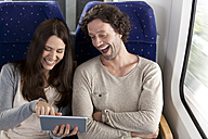 Couple using digital tablet in a train - KFF000236