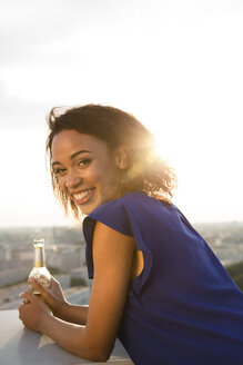 Germany, Berlin, Young woman looking at view, holding beer bottle - FKF000264