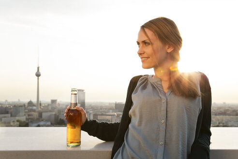 Germany, Berlin, Young woman on rooftop terrace, drinking beer - FKF000290
