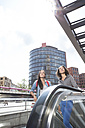 Germany, Berlin, Young women in the city, using escalator - FKF000250