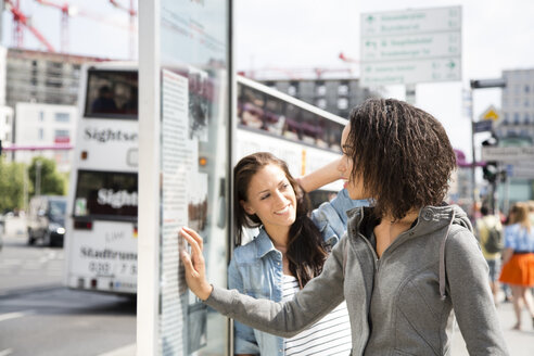 Germany, Berlin, Young women in the city, reading information panel - FKF000256