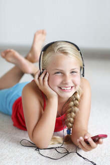 Smiling blond girl listening to music on the floor - HR000014