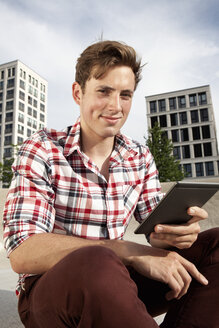 Germany, Bavaria, Munich, Young man with e-book outdoors - RBF001326