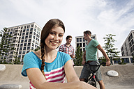 Germany, Bavaria, Munich, Smiling young woman outdoors - RBF001322