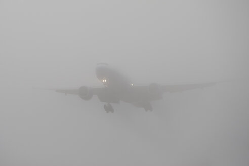 Germany, Hesse, Frankfurt, Landing airplane in fog - AM000953