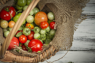 Different red and green tomatoes in basket, studio shot - SBDF000233