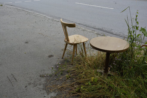 Germany, Bavaria, Riem, wooden chair and table at the roadside - AXF000506