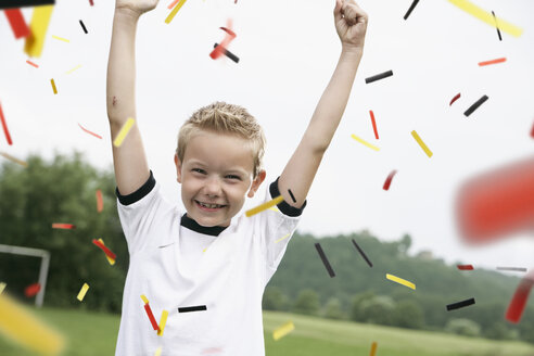 Boy in soccer jersey cheering on soccer pitch - PDF000460
