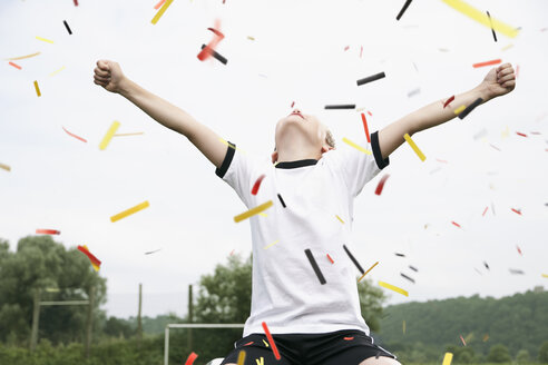 Boy in soccer jersey cheering on soccer pitch - PDF000463