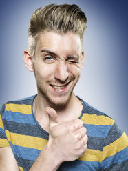 Portrait of young man with thumb up, studio shot - STKF000370