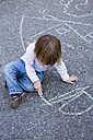 Germany, Baden-Wuerttemberg, little girl drawing with crayon on asphalt - LVF000215