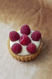 Pie with vanilla pudding and raspberries on baking paper, studio shot - CSF020128