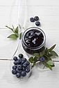 Glass of blueberry marmelade and some berries on plastic spoon, studio shot - CSF020151