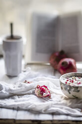 Healthy breakfast with pomegranate in yogurt, coffee and opened book - SBDF000262