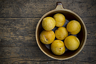 Yellow plums in ceramic bowl on wooden table, studio shot - LV000239