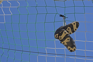 Germany, Bavaria, Munich, football shoes hanging in football net - ASF005201