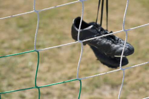 Germany, Bavaria, Munich, football shoes hanging in football net - ASF005204