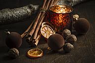 Christmas decoration with tea light candle, christmas tree balls, cinnamon sticks, slices of dried oranges and walnuts on wooden table, studio shot - SBD000265