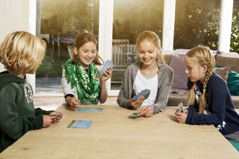 Four children playing card game in living room - GDF000219