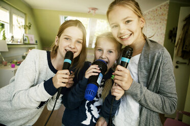 Three girls singing with microphone - GDF000227
