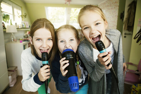 Three girls singing with microphone - GDF000229