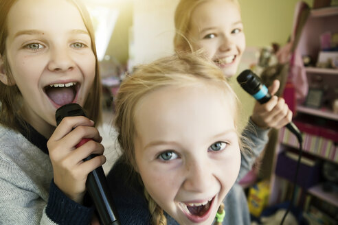 Three girls singing with microphone - GDF000230