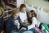 Three girls using digital tablet on bed - GDF000232