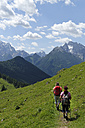 Germany, Bavaria, Hikers on Ramsau mountain pasture experience path - LB000376