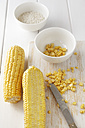 Sweetcorn cobs, corn kernels and arborio rice on white wooden table, studio shot - EVGF000245