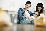 Young family with male newborn and little daughter sitting on sofa at home - JATF000384