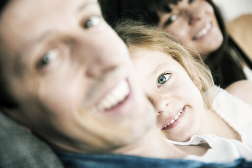Smiling young parents with little daughter sitting on sofa at home, close-up - JATF000387